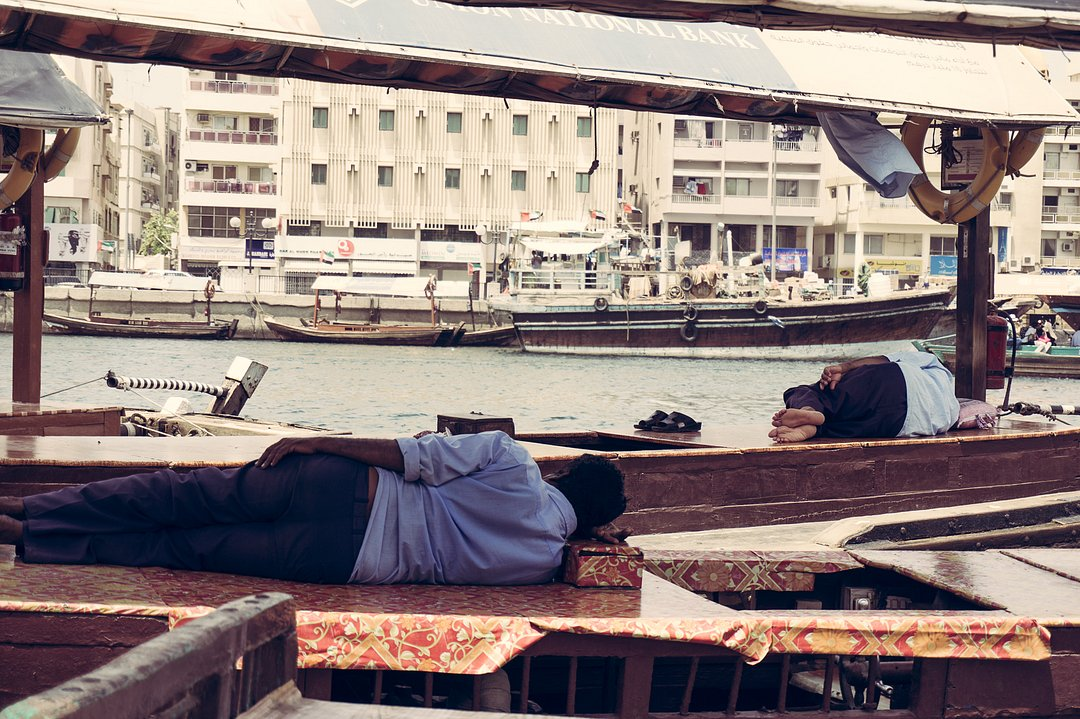 Peer at Dubai Creek - Man napping on a boat
